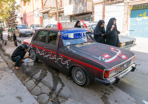 A shiite iramian man washes his car decorated for ashura celebrations to commemorate the martyrdom anniversary of hussein, Lorestan province, Khorramabad, Iran
