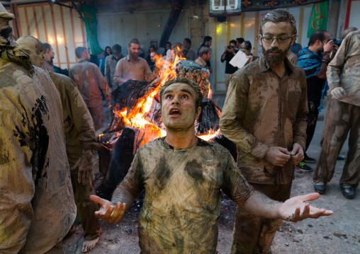 Iranian shiite muslim men gather around a bonfire after rubbing mud on their bodies during the Kharrah Mali ritual to mark the Ashura day, Lorestan Province, Khorramabad, Iran