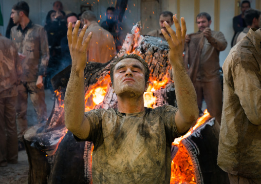 Iranian shiite muslim men pray and gather around a bonfire after rubbing mud on their bodies during the Kharrah Mali ritual to mark the Ashura day, Lorestan Province, Khorramabad, Iran