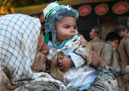 Iranian shiite muslim father rubbing mud on his baby during the kharrah mali ritual to mark the ashura day, Lorestan province, Khorramabad, Iran