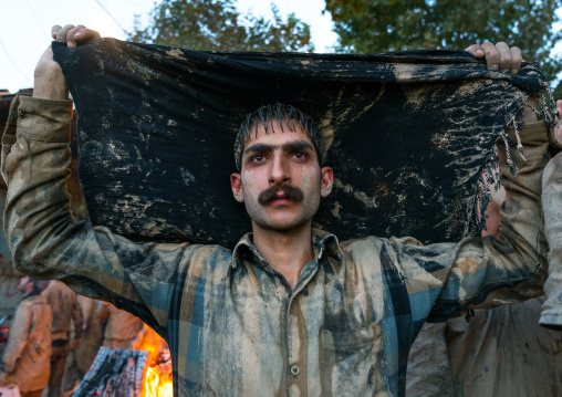 Iranian shiite muslim man drying his clothes after rubbing mud on his body during the Kharrah Mali ritual to mark the Ashura ceremony, Lorestan Province, Khorramabad, Iran