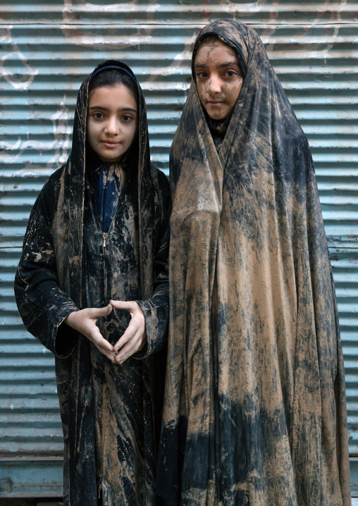 Portrait of iranian shiite muslim girls with mud stains on their chadors during the ashura day, Lorestan province, Khorramabad, Iran