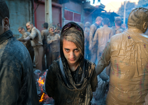 An iranian shiite muslim woman stands in front a bonfire after rubbing mud on her chador during the kharrah mali ritual to mark the ashura day, Lorestan province, Khorramabad, Iran