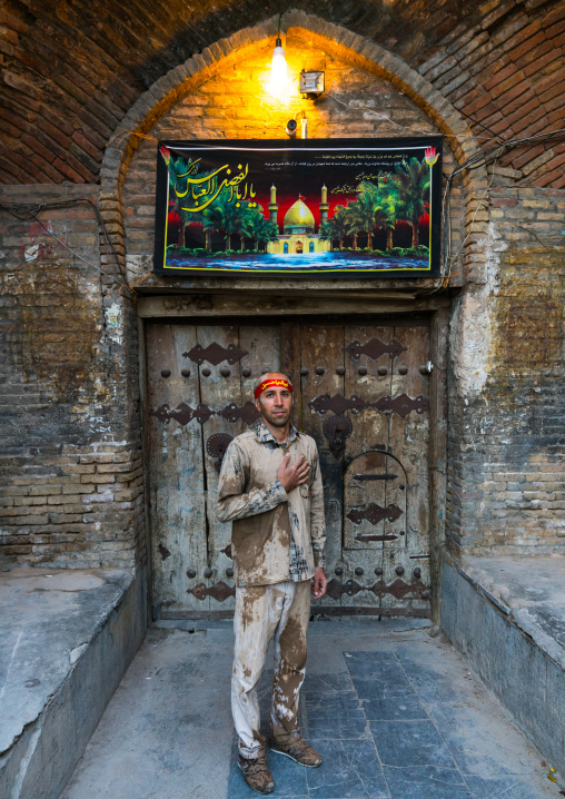 Iranian shiite muslim man standing in front of an old wooden door after rubbing mud on his clothes during the Kharrah Mali ritual to mark the Ashura ceremony, Lorestan Province, Khorramabad,