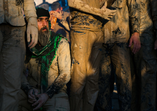 Iranian shiite muslim men gather around a bonfire after rubbing mud on their clothes during the Kharrah Mali ritual to mark the Ashura day, Lorestan Province, Khorramabad, Iran