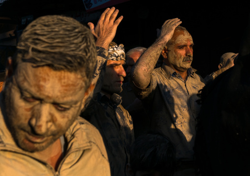 Iranian shiite muslim men with mud stains during the ashura day, Lorestan province, Khorramabad, Iran