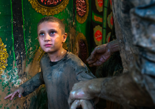 Iranian shiite muslim boy after rubbing mud on his body during the Kharrah Mali ritual to mark the Ashura day, Lorestan Province, Khorramabad, Iran