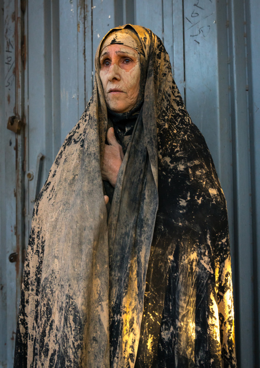 Iranian shiite muslim woman after rubbing mud on her chador during the kharrah mali ritual to mark the ashura ceremony, Lorestan province, Khorramabad, Iran