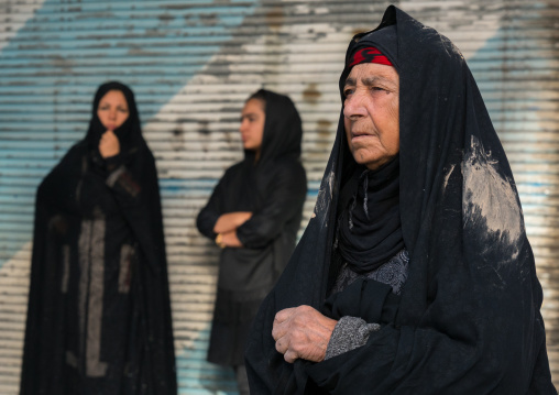 Iranian shiite muslim women with mud stains on their chadors during the Ashura ceremony, Lorestan Province, Khorramabad, Iran