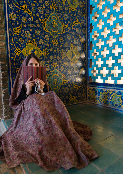 A young adult woman reads a book inside masjed-e Sheikh Lotfallah, Isfahan Province, Isfahan, Iran