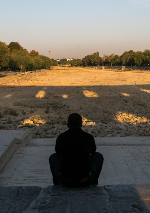 Iranian man sit on Khaju bridge Pol-e Khaju looking the  dry Zayandeh river, Isfahan Province, Isfahan, Iran