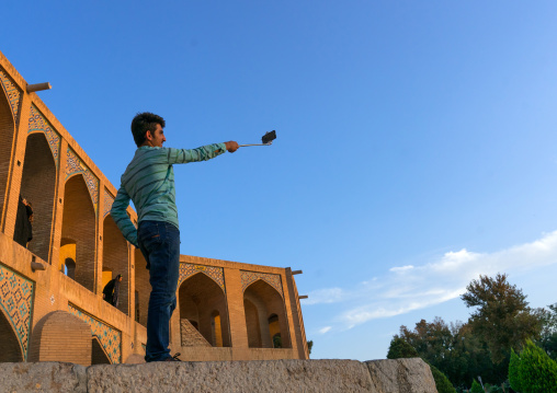 Iranian man taking a selfie on khaju bridge pol-e khaju, Isfahan province, Isfahan, Iran