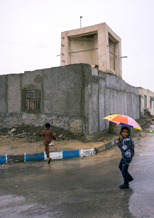 children under the rain in front of a wind tower, Qeshm Island, Salakh, Iran