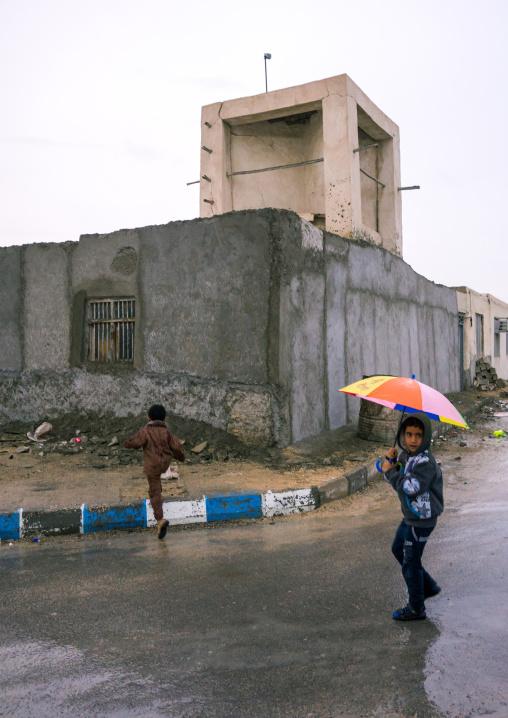 children under the rain in front of a wind tower, Qeshm Island, Salakh, Iran