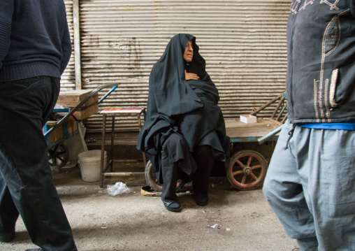 Old woman sitting on a bench in the bazaar, Central district, Tehran, Iran