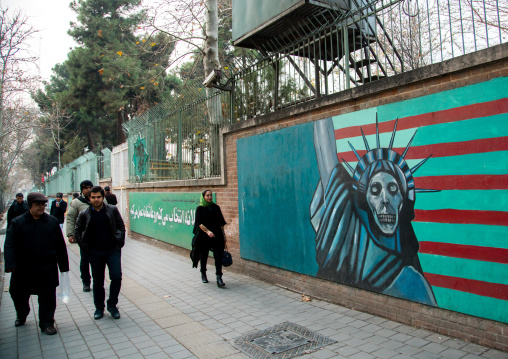 people passing in front of anti-american mural propoganda slogan depict statue liberty skeleton on the wall of the former united states embassy, Central district, Tehran, Iran