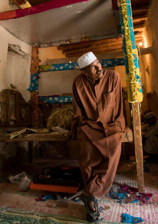 Man sitting on the bed of a wedding room, Qeshm island, Tabi, Iran