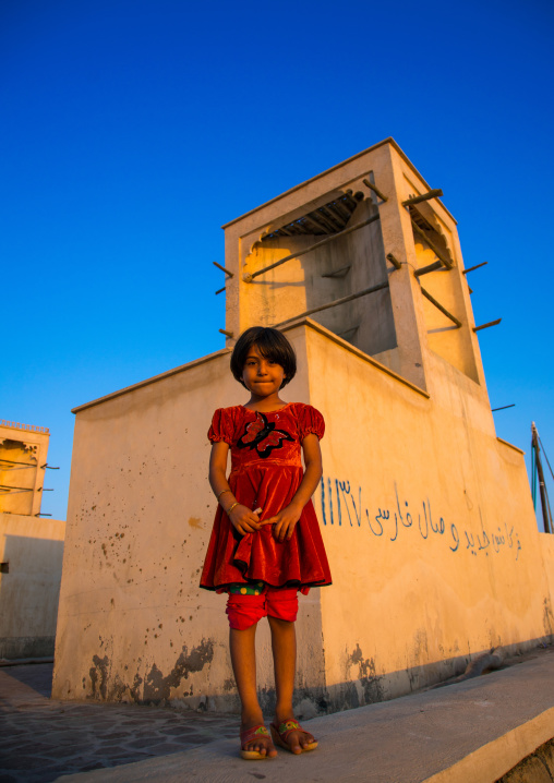 Little girl in front of a wind tower used as a natural cooling system, Qeshm island, Laft, Iran