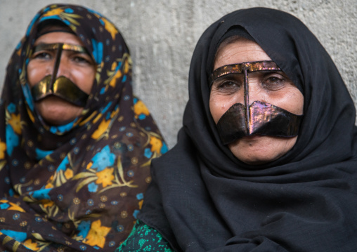 Bandari women wearing the traditional masks called the burqas with a moustache shape, Qeshm island, Salakh, Iran