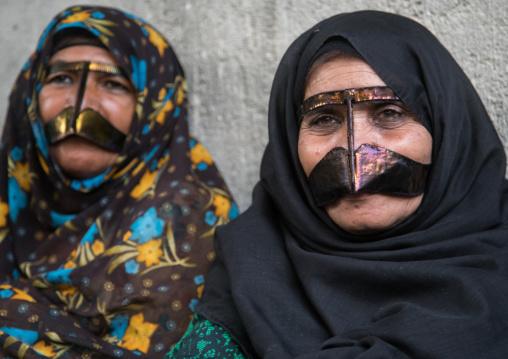 bandari women wearing the traditional masks called the burqas with a moustache shape, Qeshm Island, Salakh, Iran