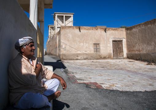 man sitting in front of a wind tower, Hormozgan, Bandar-e Kong, Iran