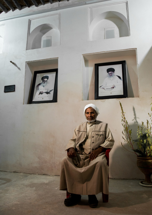 old bandari sailor in front of khameini and khomeini portraits in a house, Hormozgan, Bandar-e Kong, Iran