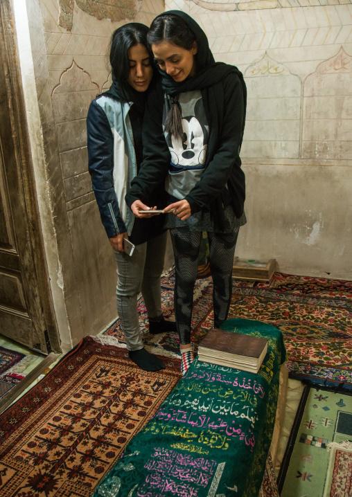 iranian women taking selfie in the meditation room of the tomb of shah nematollah vali, Kerman province, Mahan, Iran