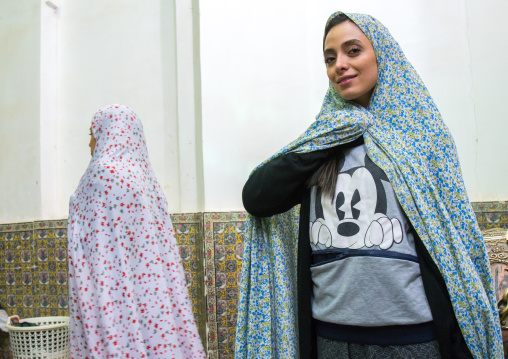 Iranian woman with a mickey mouse shirt in the tomb of shah nematollah vali, Kerman province, Mahan, Iran