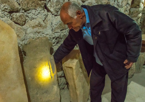 Old man showing an albatre tombstone in his troglodyte house, Kerman province, Meymand, Iran