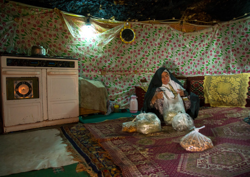 Old widow woman in her troglodyte house packing herbs, Kerman province, Meymand, Iran