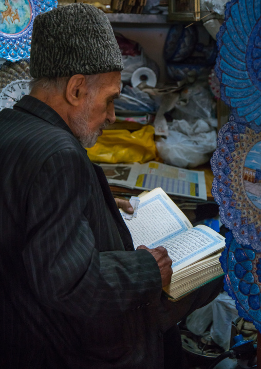 old man reading koran in his shop, Isfahan Province, isfahan, Iran