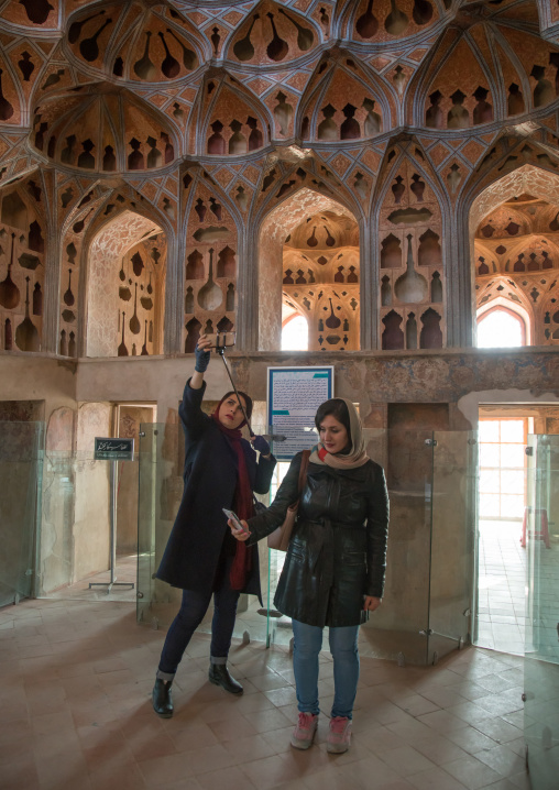 iranian women taking selfie picture in the acoustic ceiling in the music room of ali qapu palace, Isfahan Province, isfahan, Iran