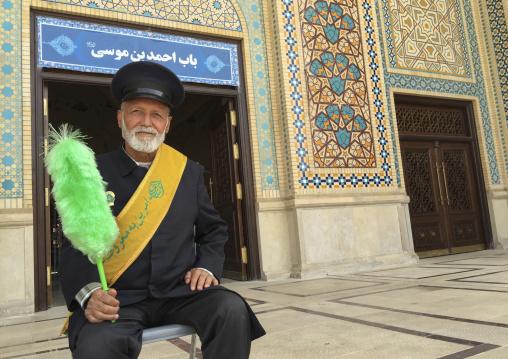 Guard with a green feather duster at the shah-e-cheragh mausoleum, Fars province, Shiraz, Iran