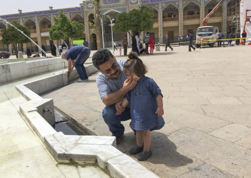 Father and daughter making ablutions in the shah-e-cheragh mausoleum, Fars province, Shiraz, Iran