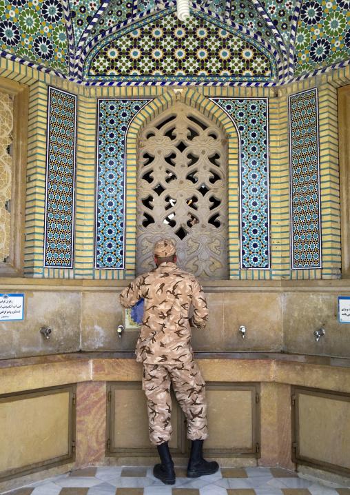 Soldier taking water at a fountain at the shah-e-cheragh mausoleum, Fars province, Shiraz, Iran