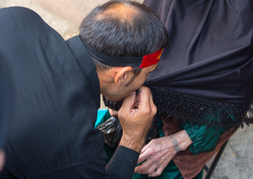 Shiite Man Kissing The Dark Clothes Of His Mother For Chehel Menbari Festival On Tasua Day To Commemorate The Martyrdom Of Hussein, Lorestan Province, Khorramabad, Iran