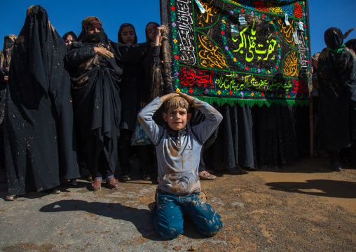 Iranian Shiite Muslim Women Covered In Mud In Front Of A Boy Praying On His Knees During Ashura, The Day Of The Death Of Imam Hussein, Kurdistan Province, Bijar, Iran
