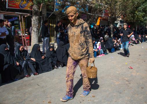 Iranian Shiite Muslim Man Covered In Mud With A Bucket During Ashura Day, Kurdistan Province, Bijar, Iran
