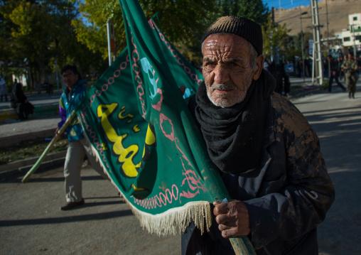 Iranian Shiite Muslim Man Covered In Mud Carrying A Flag During Ashura Day, Kurdistan Province, Bijar, Iran