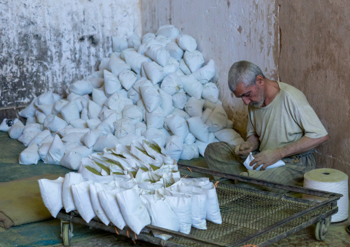 Iranian Worker Packing Henna Bags In A Traditional Mill, Yazd Province, Yazd, Iran