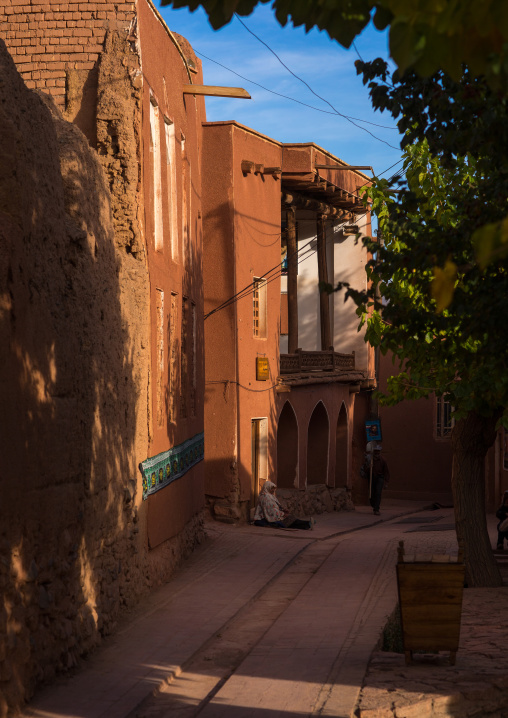 Sitting Woman Sitting In Front Of An Ancient Building With Ashura Decoration In Zoroastrian Village, Isfahan Province, Abyaneh, Iran
