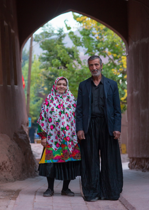 Portrait Of An Iranian Woman Wearing Traditional Floreal Chador With Her Husband In Zoroastrian Village, Isfahan Province, Abyaneh, Iran