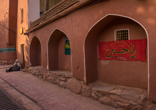 Woman Sitting In Front Of An Ancient Building With Ashura Decoration In Zoroastrian Village, Isfahan Province, Abyaneh, Iran