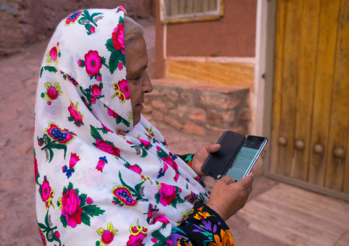 Portrait Of An Iranian Woman Wearing Traditional Floreal Chador And Texting On Her Mobile Phone, Isfahan Province, Abyaneh, Iran