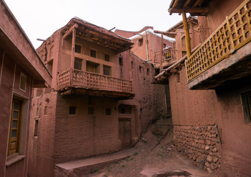 Iranian Woman Standing At The Balcony Of An Ancient Building In Zoroastrian Village, Isfahan Province, Abyaneh, Iran
