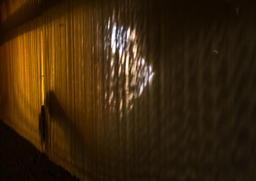 Silhouette Of An Afghan Refugee Woman Making A Carpet In Her House, Isfahan Province, Kashan, Iran