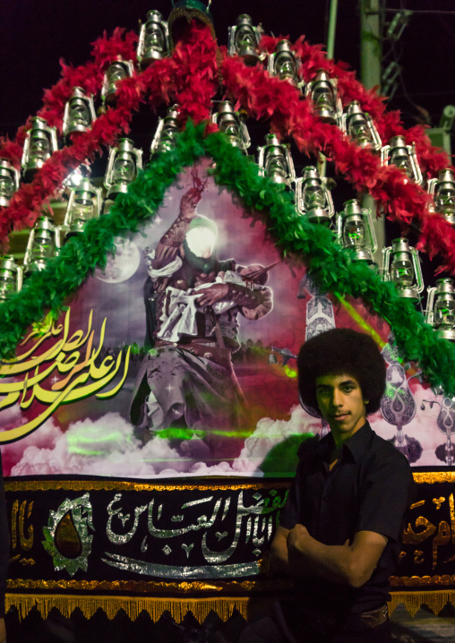 Young Iranian Shiite Muslim Man Mourner Pausing Proudly In Front Of An Alam On Ashura, The Day Of The Death Of Imam Hussein, Isfahan Province, Kashan, Iran