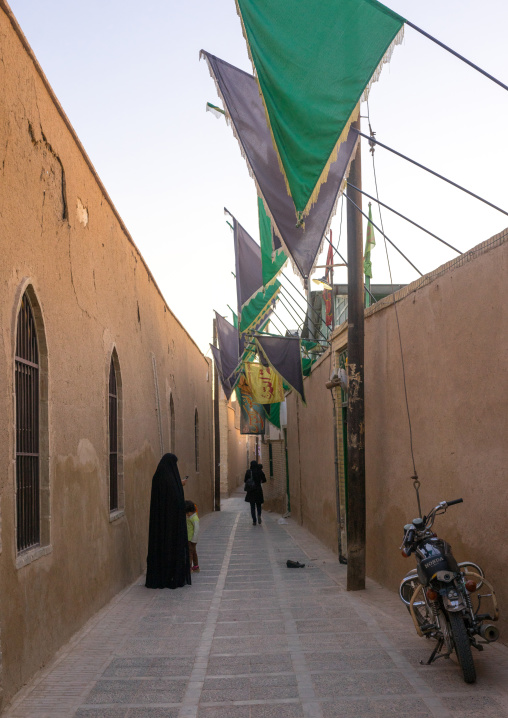 Muslim Women In A Narrow Street With Green Flags, Yazd Province, Yazd, Iran