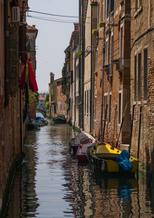 Venetian decayed facades and reflections on a canal, Veneto Region, Venice, Italy