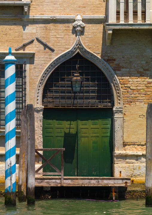 Old door on the canal, Veneto Region, Venice, Italy